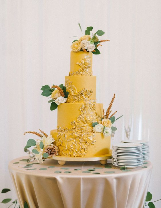an elegant yellow wedding cake with gold textural patterns, white and yellow blooms and greenery