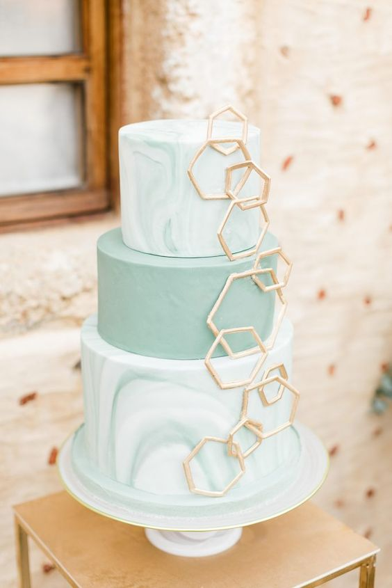 an olive green wedding cake with marble and usual tiers, with gold hexagons covering them is a very beautiful idea