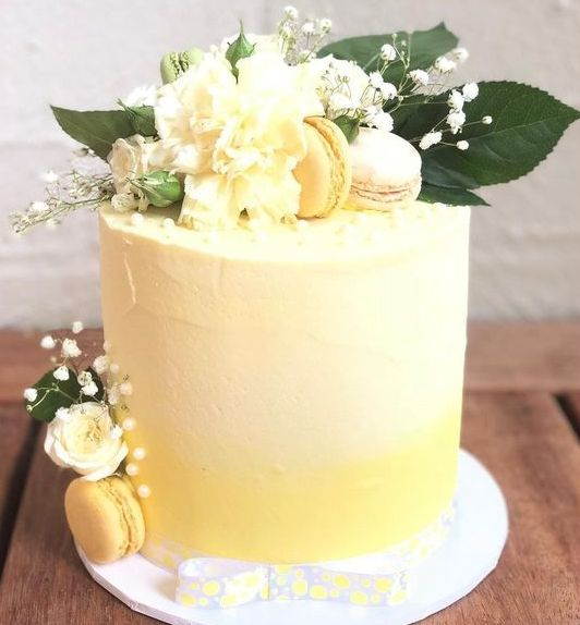 an ombre yellow wedding cake with textural buttercream, white and yellow blooms, macarons and foliage is a bold and cool idea