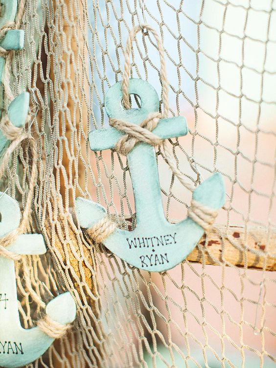 aqua-colored plywood anchors with names and rope on fishing net are very creative and bright pieces to rock