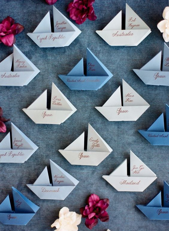 blue, grey and white paper boats as escort cards and wedding favors at the same time are a cool idea
