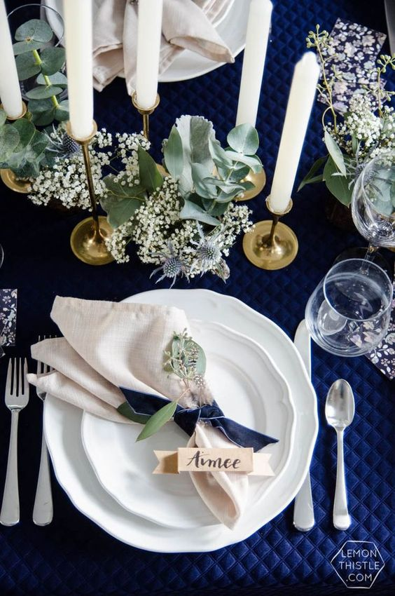 bold navy, cremay and gold wedding tablescape with white blooms and thistles and lots of white candles