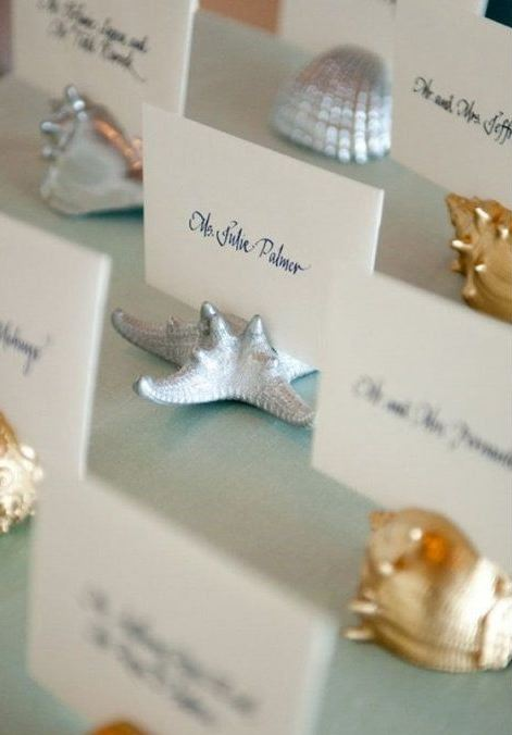 gold and silver sea creature figurines holding escort cards are very chic and timeless for a beach wedding