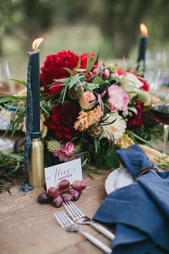 gold candle holders, navy candles and napkins, a brigth floral centerpiece