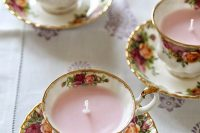 lovely floral teacups with candles inside can hold your escort cards and become chic wedding favors