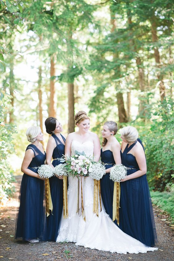 navy maxi bridesmaid dresses with baby's breath bouquets and gold ribbons