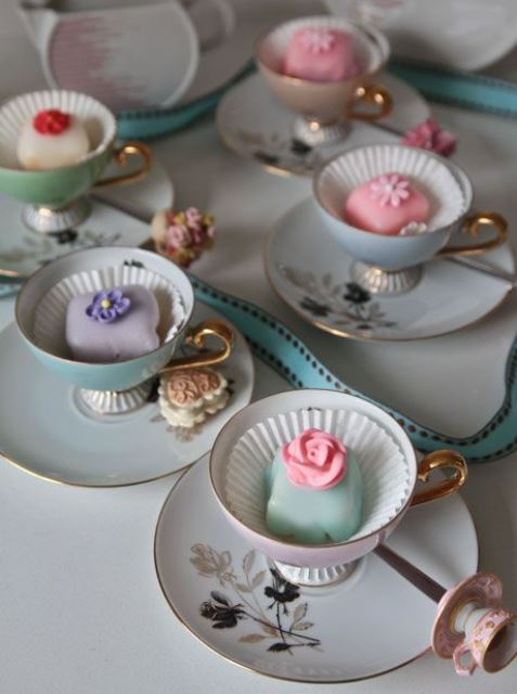pastel teacups with pastel petit fours are great wedding favors and they can hold your escort cards, too