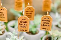 simple teacups with succulents and escort cards designed as teabags on holders is a cool idea