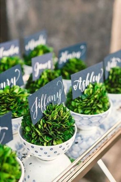 vintage polka dot teacups with fresh greenery and cool chalkboard escort cards can double as favors