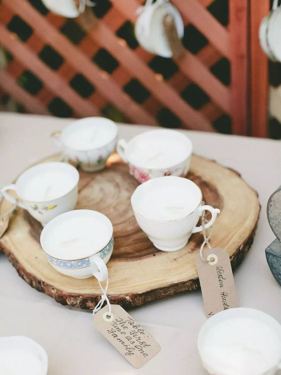 vintage teacups with cardboard escort cards placed on wooden slices are a lovely idea for a rustic wedding