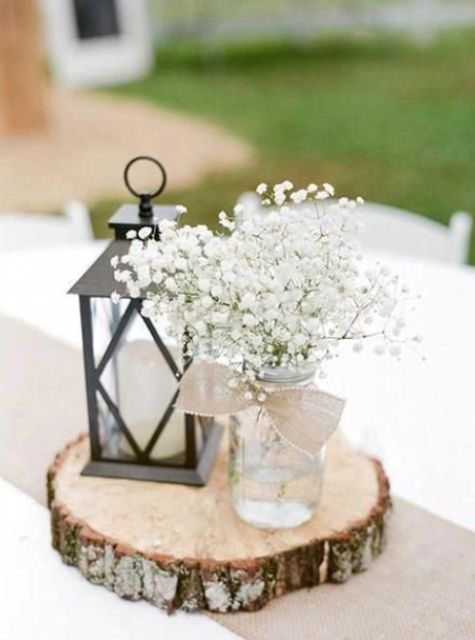 a barn wedding centerpiece of a wood slice, a candle lantern, a jar with a burlap bow and baby's breath