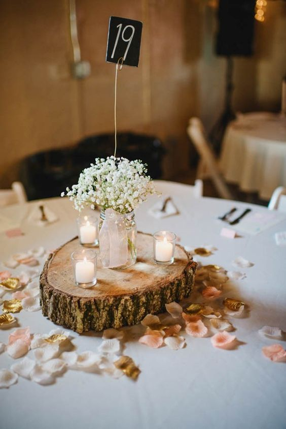 a barn wedding centerpiece of a wood slice, petals, candles and baby's breath in a jar plus a chalkboard table number