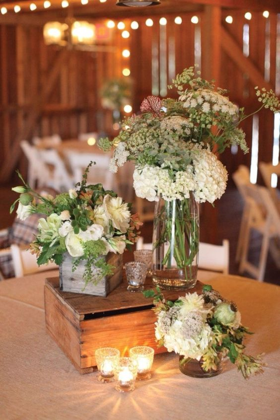 a barn wedding centerpiece of candles, neutral blooms and greenery plus succulents and a wooden box