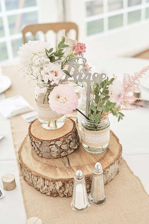 a barn wedding centerpiece of wood slices, jars wrapped with burlap and lace, neutral blooms and greenery and a calligraphy table number