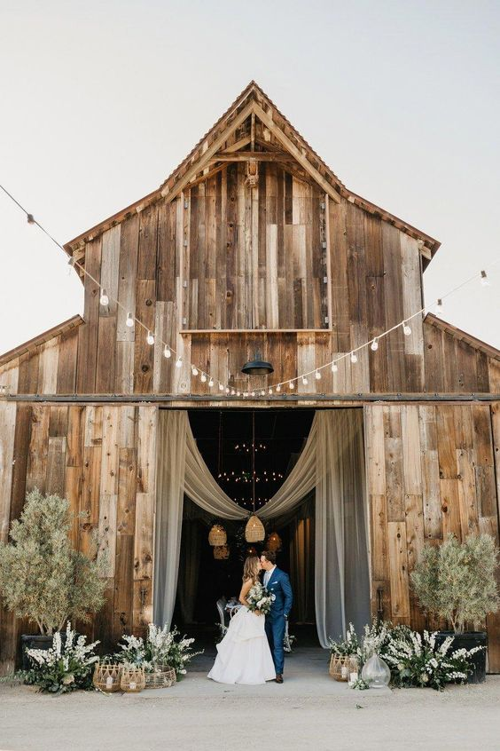 a barn wedding ceremony space with white florals and greenery arrangements, candle lanterns and potted trees plus a fabric decoration