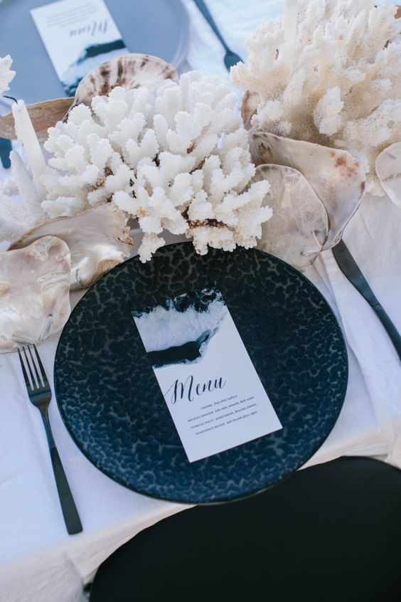 a beach bridal shower table with bold printed plates, corals, seashells and black cutlery for a modern feel