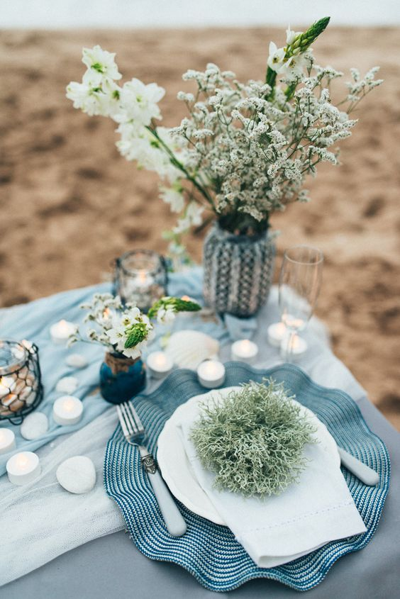 a beach bridal shower tablescape with pebbles, tealights, neutral blooms and greenery and candle lanterns