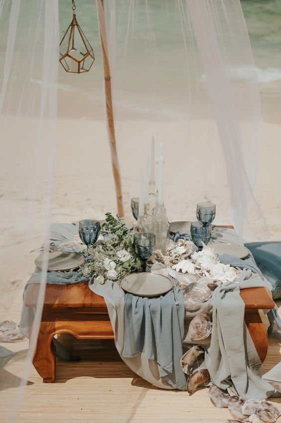 a beach wedding picnic with a low table, airy blue and grey runners, blue glasses, greenery, shells and corals