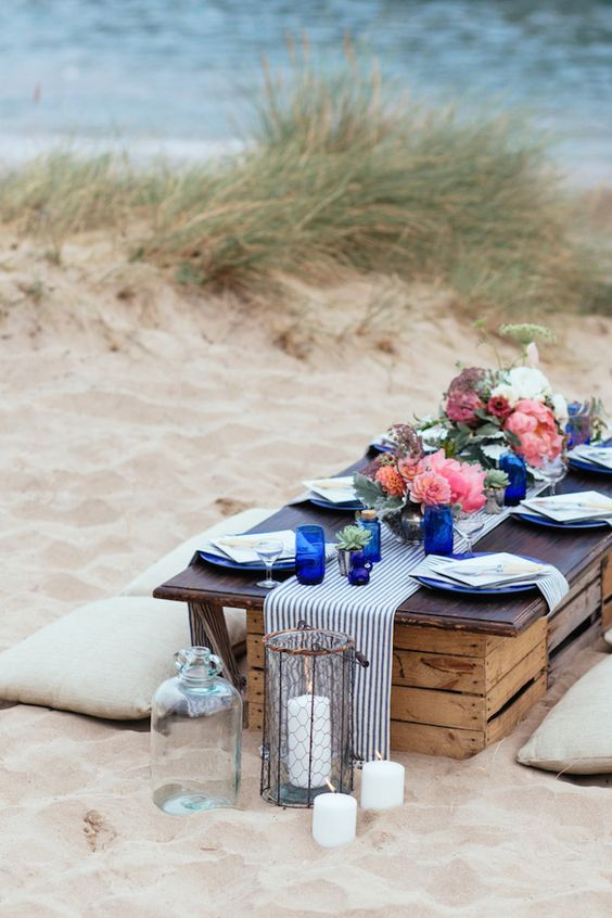 a beach wedding picnic with a low table, pillows, candles, bright blooms, blue vases and striped linens