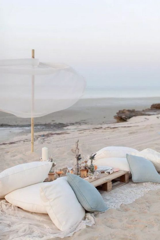 a beach wedding picnic with a pallet table, white and blue pillows, pillar candles, neutral blooms and candles