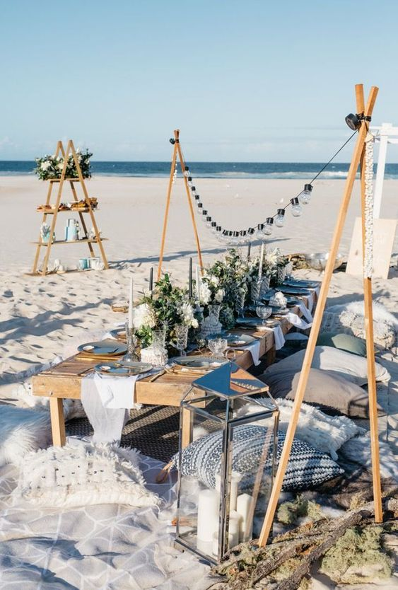 a beach wedding picnic with lights, a low table, lots of pillows, greenery and white blooms, neutral candles