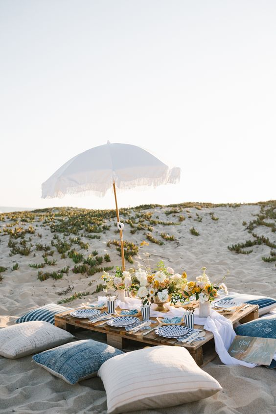 a beach wedding picnic with white and blue pillows, an airy runner, neutral blooms and greenery, an umbrella
