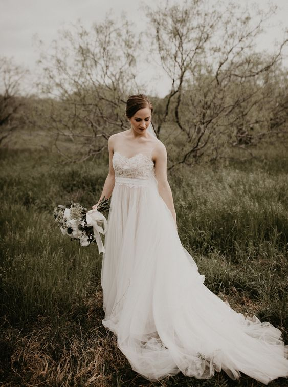 a beautiful and romantic wedding dress with no sleeves, an illusion neckline and a layered tulle skirt with a trian