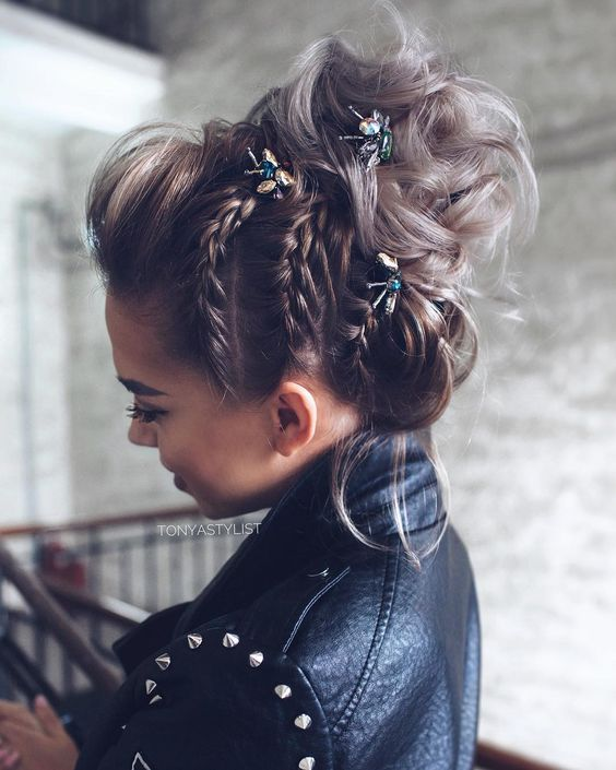a beautiful braided and wavy top knot with colorful rhinestone hairpieces and a volume on top is very badass