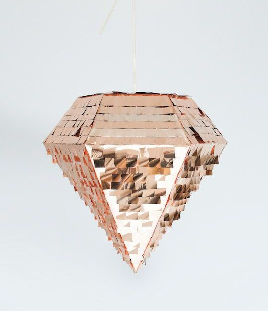 a beautiful rose gold diamond-shaped pinata is a very pretty and shiny alternative to a usual wedding guest book