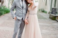 a blush A-line wedding dress with a lace bodice, a plunging neckline, long sleeves and a layered skirt plus a train