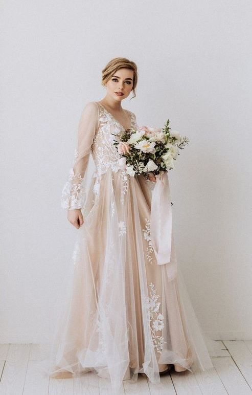 a blush A line wedding dress with a v neckline, puff sheer sleeves and white floral appliques for a spring bride