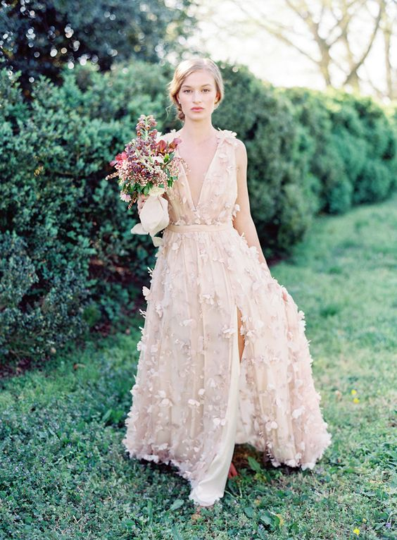 a blush A line wedding dress with floral appliques and plunging neckline plus a front slit for a romantic bride