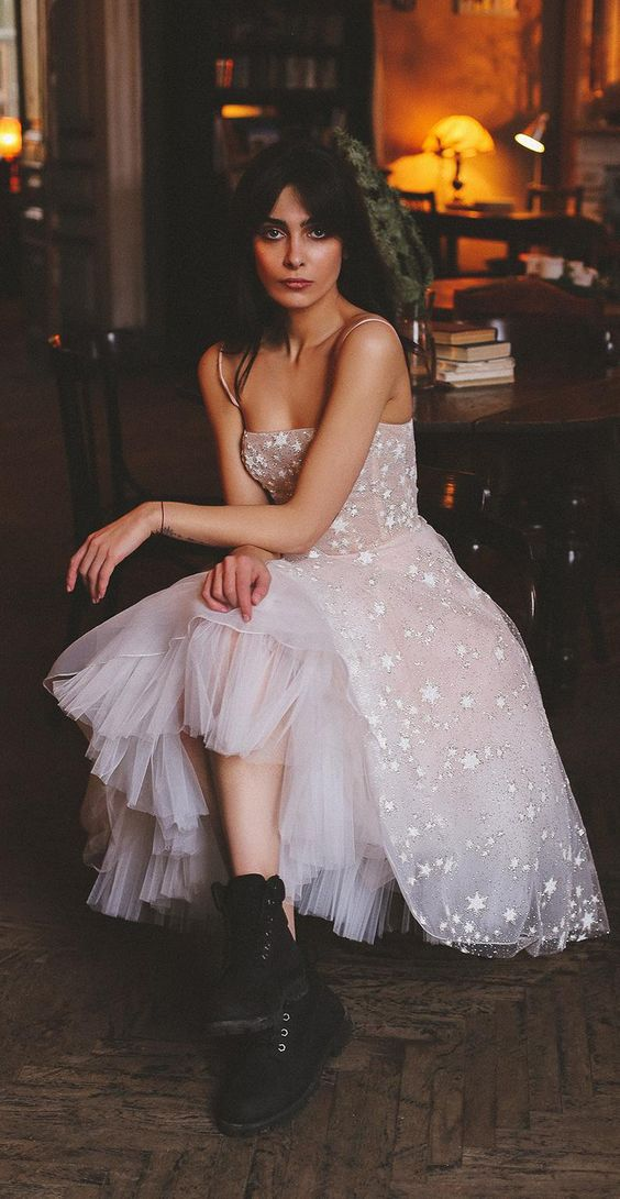 a blush A-line wedding dress with spaghetti straps, a full skirt and star appliques for a celestial bride