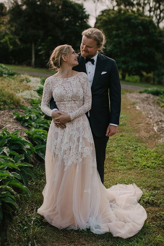 a blush A-line wedding dress with white lace with long sleeves, a high neckline and a train is very romantic
