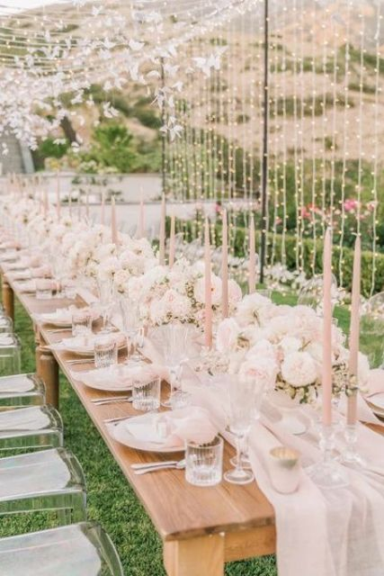 a blush garden bridal shower reception with a light tunnel over it, with blush linens and candles and with blush blooms is dreamy