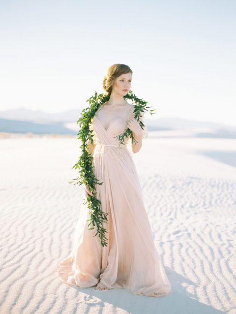 a blush spaghetti strap draped wedding gown with an A line skirt, sheer cap sleeves and a draped bodice