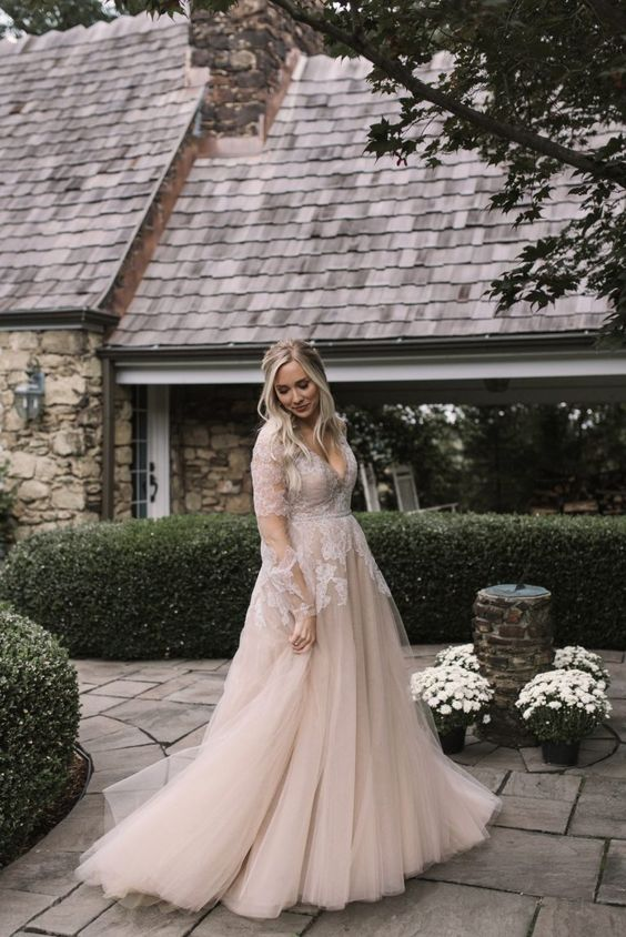a blush wedding dress with a deep V neckline, illusion sleeves and white lace appliques for a romantic bride