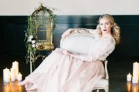 a blush wedding dress with a lace applique bodice and sleeves and a layered skirt looks cool with a dark lip