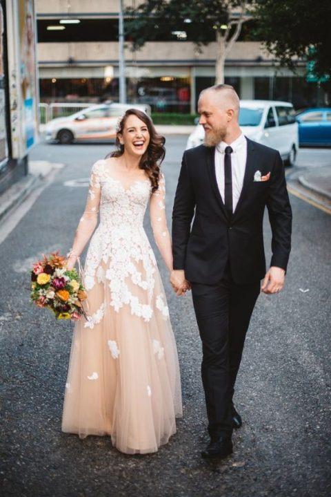 a blush wedding dress with an illusion neckline, sleeves and white floral appliques all over the dress that make it edgy