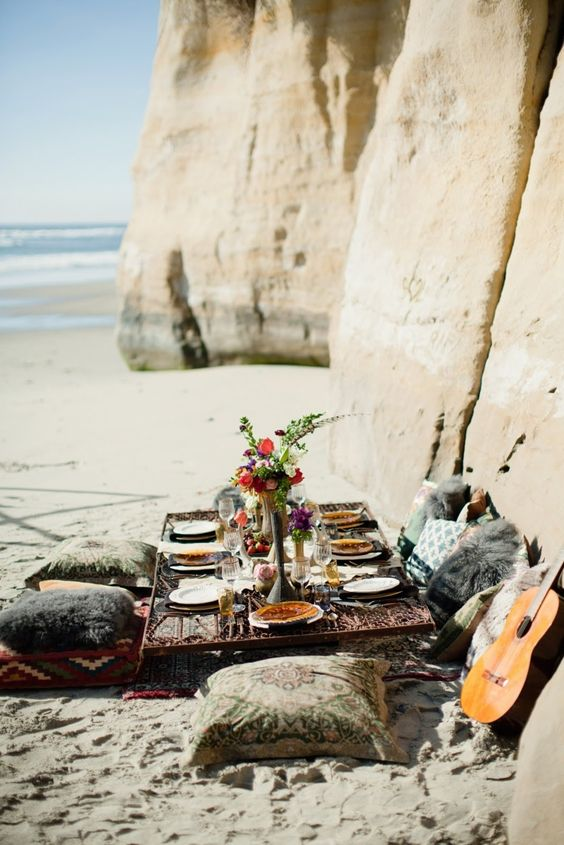 a boho beach bridal shower picnic with bold printed and fur pillows, bright blooms and delicious food