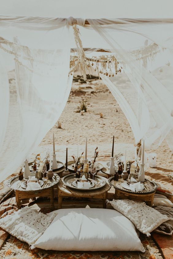 a boho desert wedding picnic with trays, candles, pillows, dried flowers and pampas grass and airy curtains