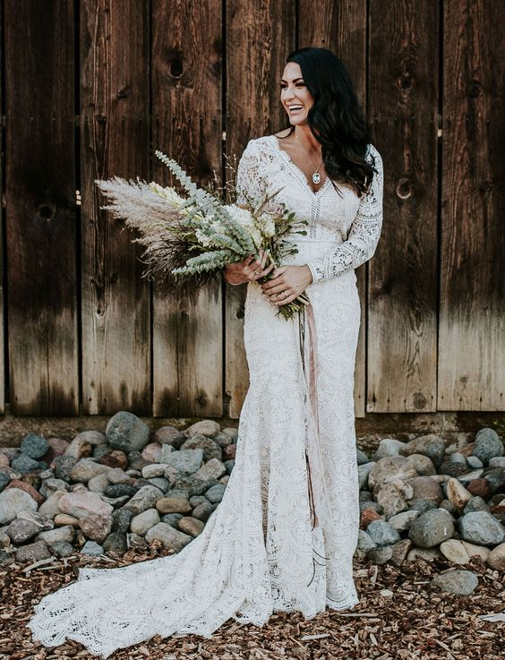 a boho lace mermaid wedding dress with long sleeves and a train plus a V-neckline for a boho barn bride