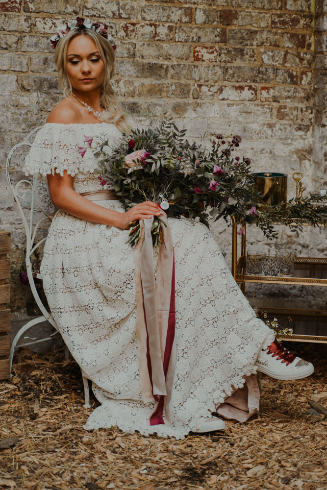a boho lace off the shoulder wedding dress with a silk sash and a statement necklace plus sneakers