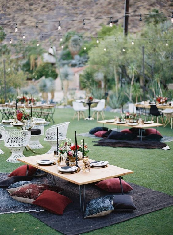 a boho wedding picnic in dark and jewel tones, with low hairpin tables, bright pillows, black candles and bright blooms
