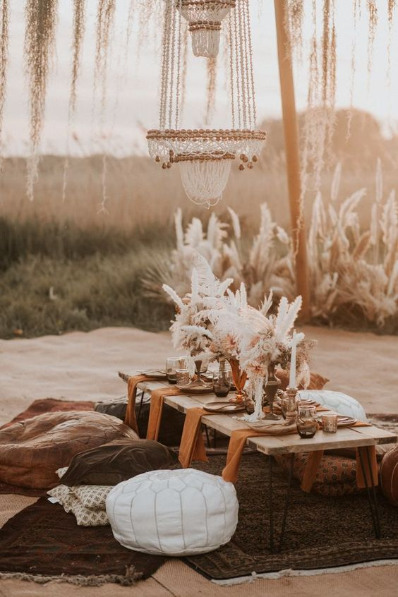 a boho wedding picnic setting with a large chandelier, pampas grass, candles, pillows and a white leather ottoman