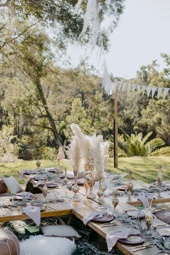 a boho wedding picnic with a cross table, pampas grass, neutral air plants, pastel linens for a spring celebration