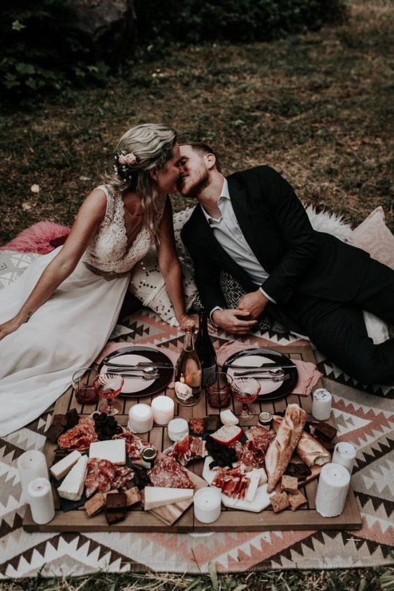 a boho wedding picnic with a printed blanket, a low crate table, pillar candles and a delicious grazing table