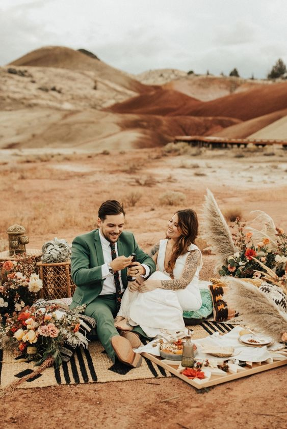 a boho wedding picnic with a printed blanket, a tray table, floral arrangements and dried florals, pampas grass