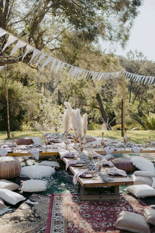 a boho wedding picnic with low tables, white pillows, leather ottomans, pampas grass, candles and paper buntings