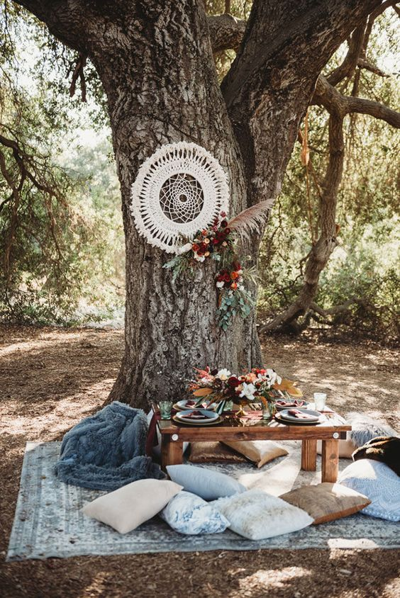 a boho woodland wedding picnic with a dream catcher, bright blooms and pampas grass, a low table, pastel pillows and colored glasses